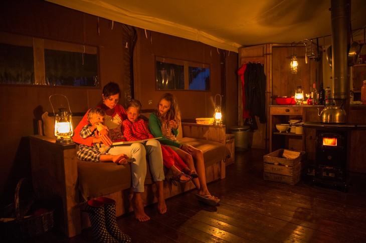 Мама читает детям книжку в полумраке
