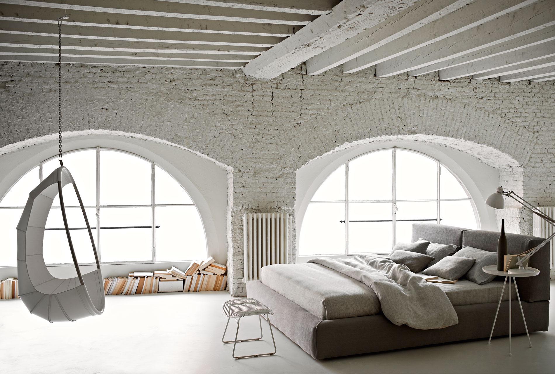 Каменные стены и арочные окна - необычное оформление спальни