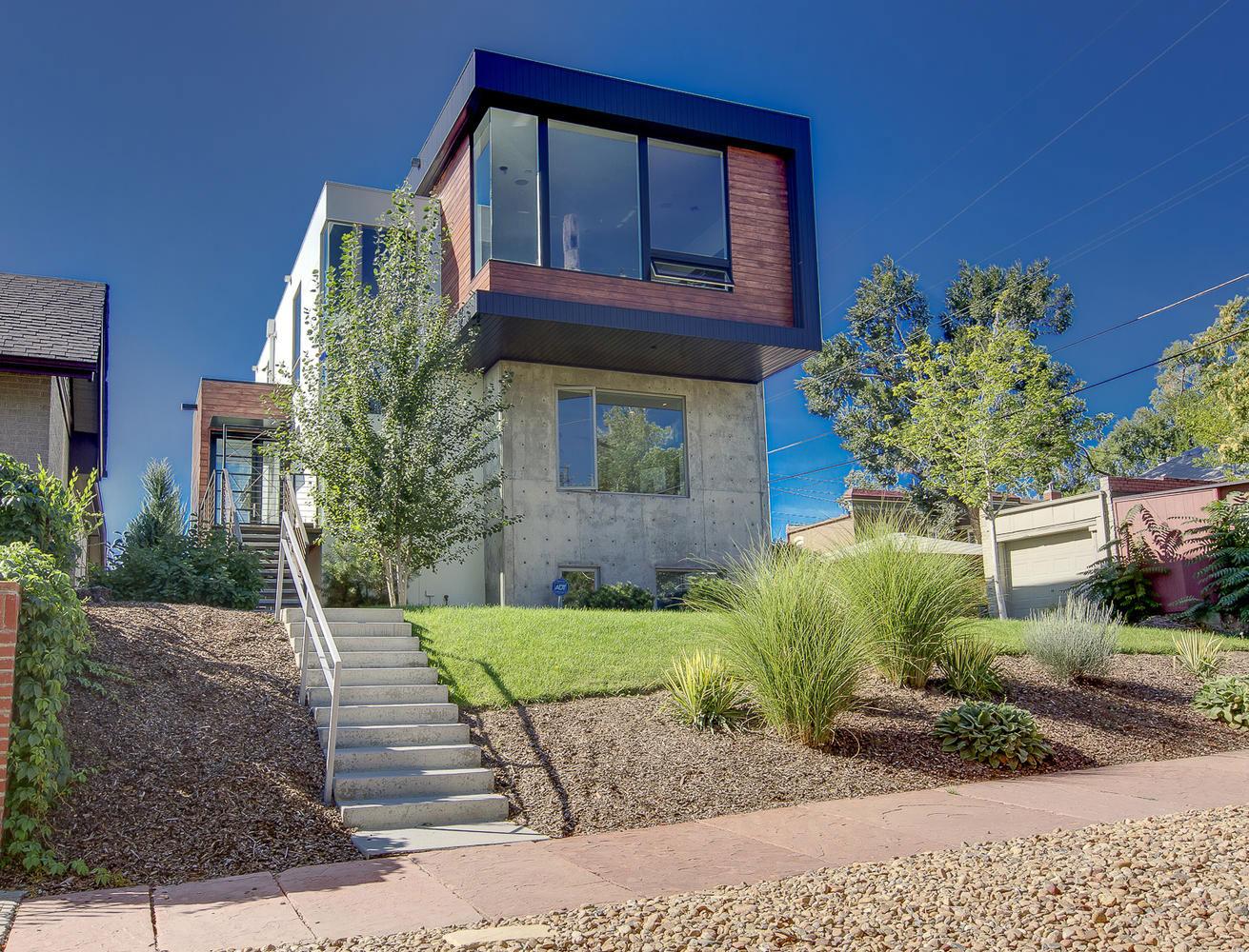 Американские дома: фото стильного коттеджа переменной этажности с ярким фасадом