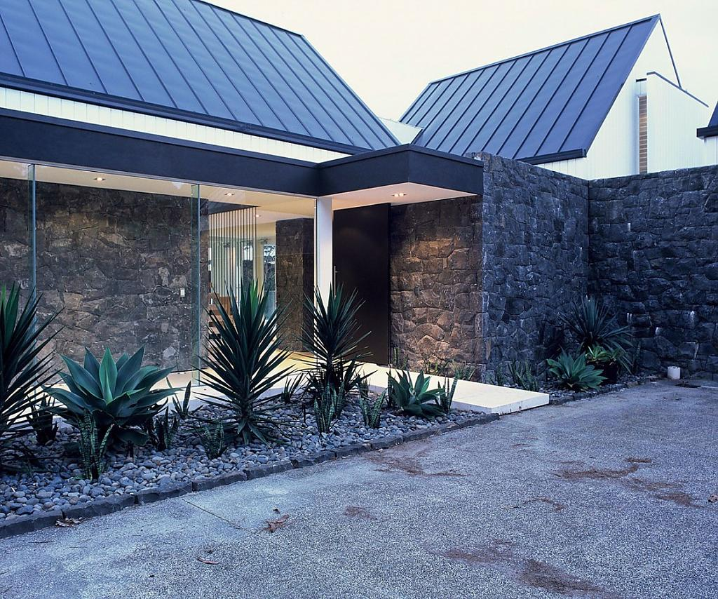 Дом со стеклянными стенами, синей крышей и современным интерьером в Окленде