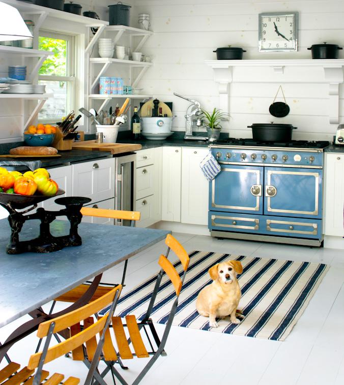 Синяя плита среди белоснежной кухонной мебели