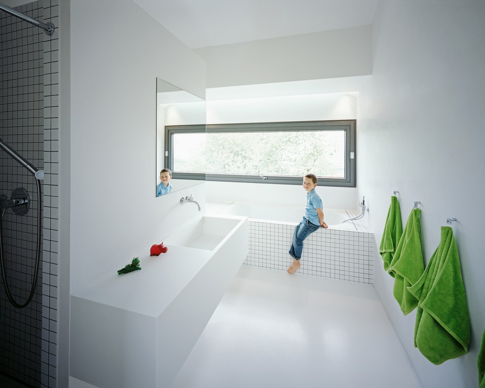 Просторная белая ванная с ярко-зелеными полотенцами