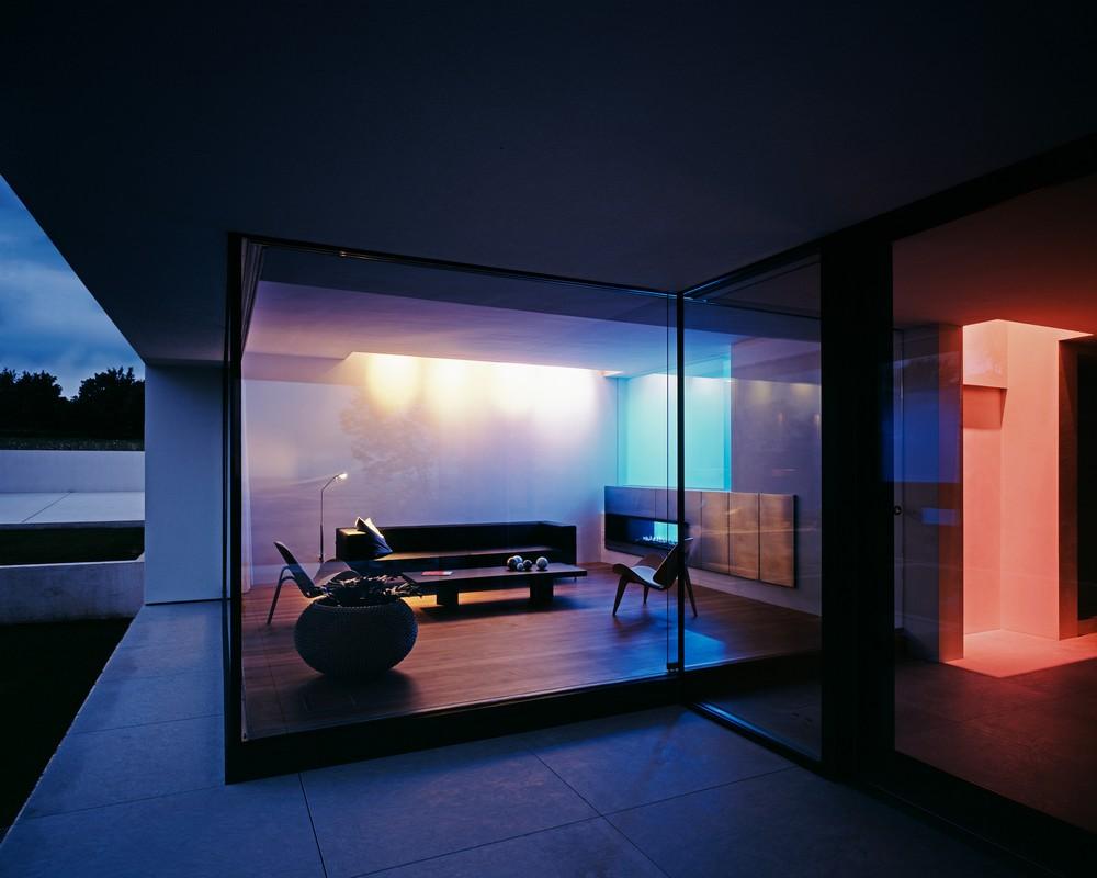 Со двора через прозрачную стену видно гостиную