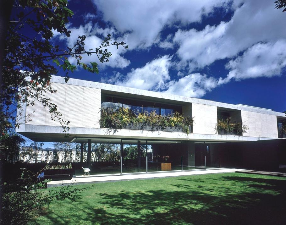 Г-образный дом в три этажа с красивым садом и бассейном