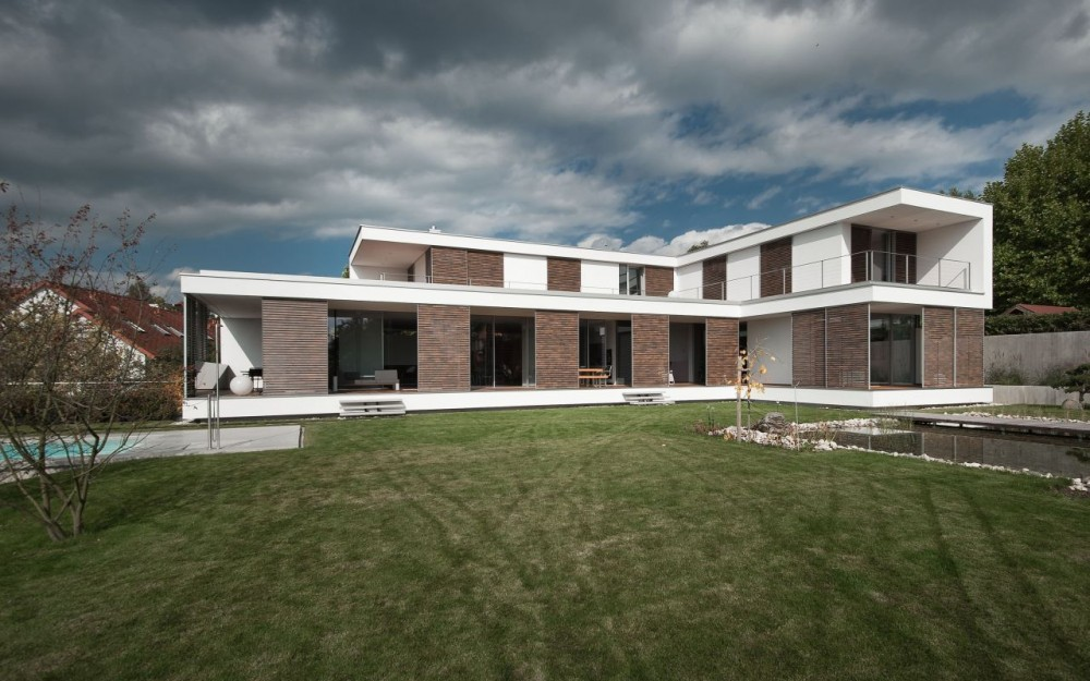 Г-образный проект дома с террасами и большим бассейном