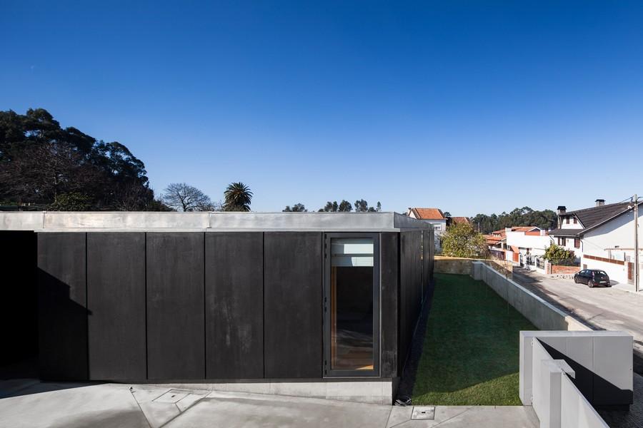Проект небольшого загородного дома с тёмным фасадом и террасой на крыше